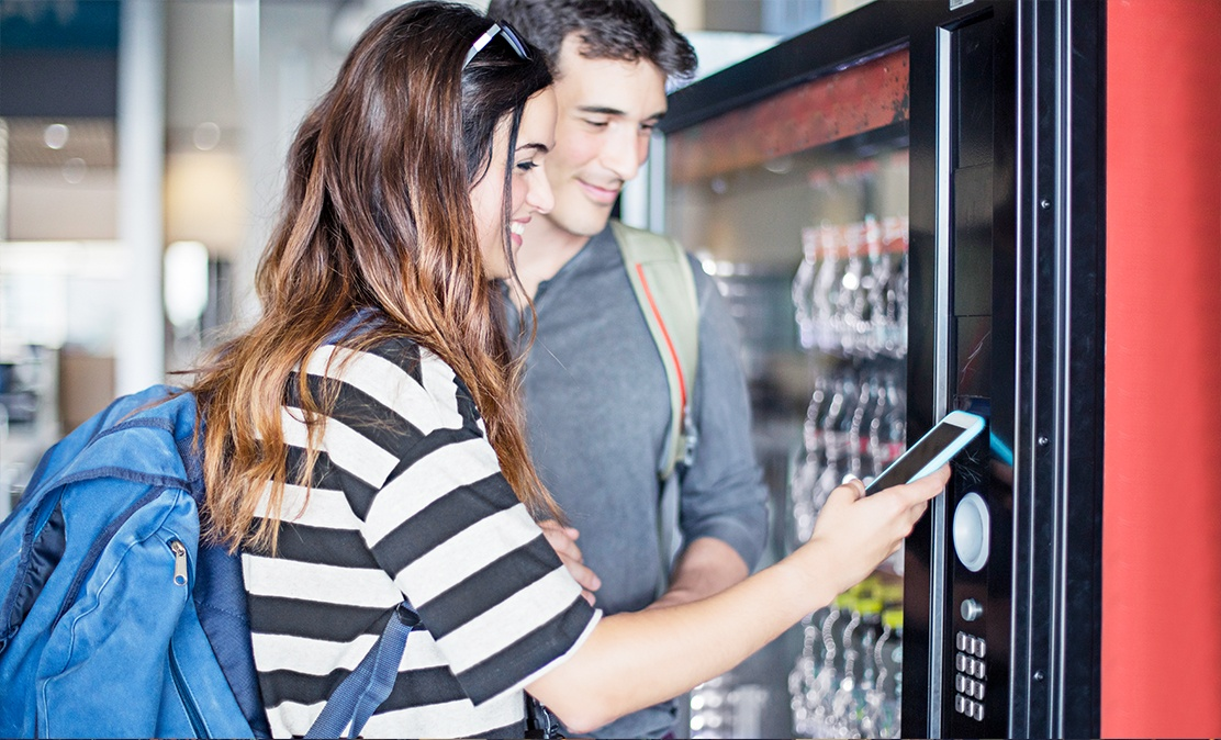young couple with backpacks using iot hardware phone to pay for soda at machine