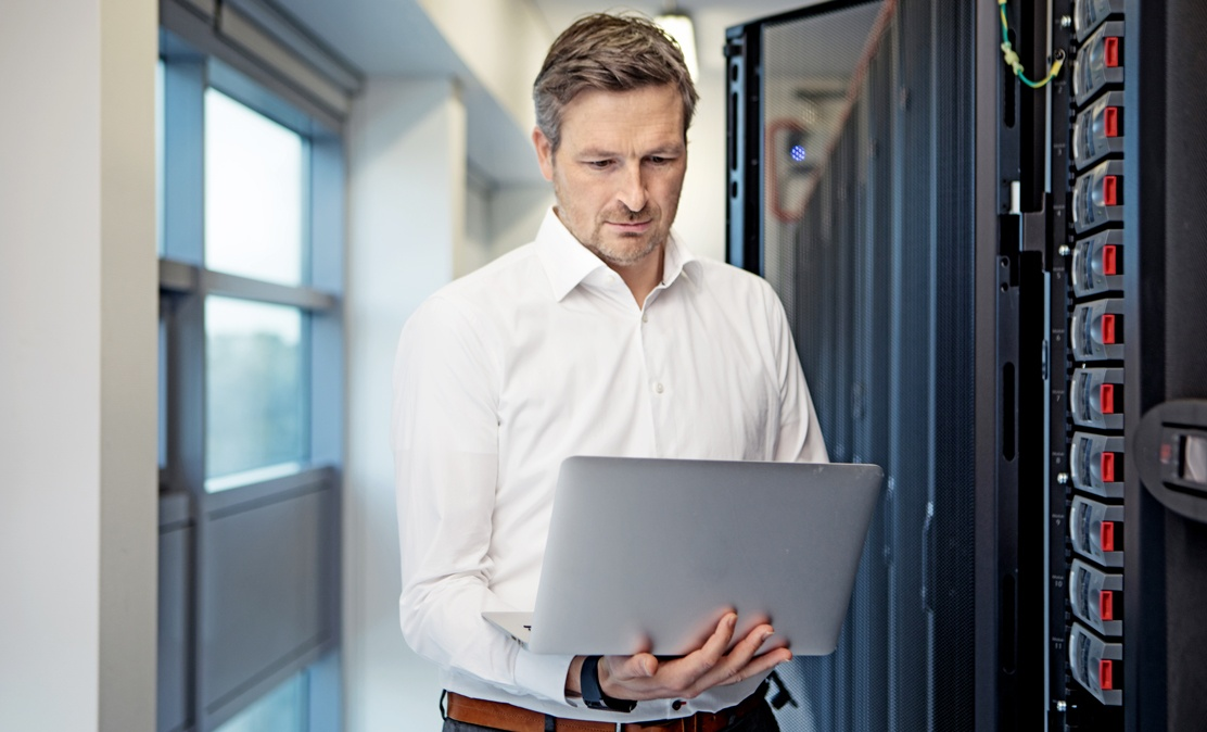man types on laptop to monitor iot security next to servers