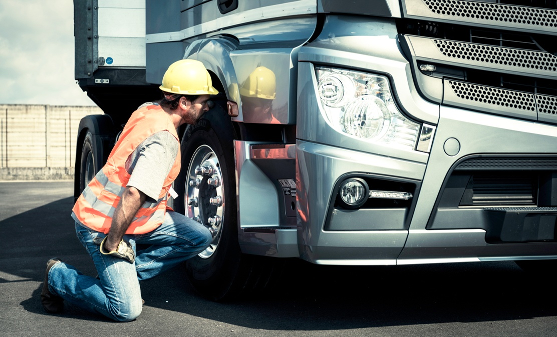 man in orange safety vest kneels to look in wheel well of semi-truck with iot vehicle tracking