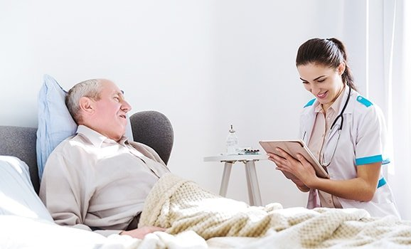 woman uses tablet with iot healthcare solutions at bedside of senior man