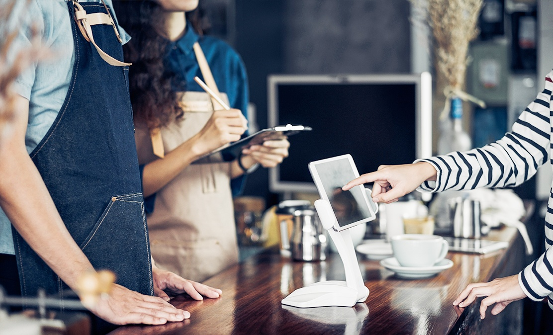 woman uses iot hardware tablet at coffee shop to make a payment