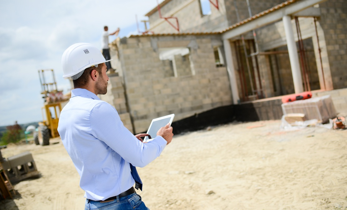 man standing at construction site wearing white hard hat and holding iot devices tablet