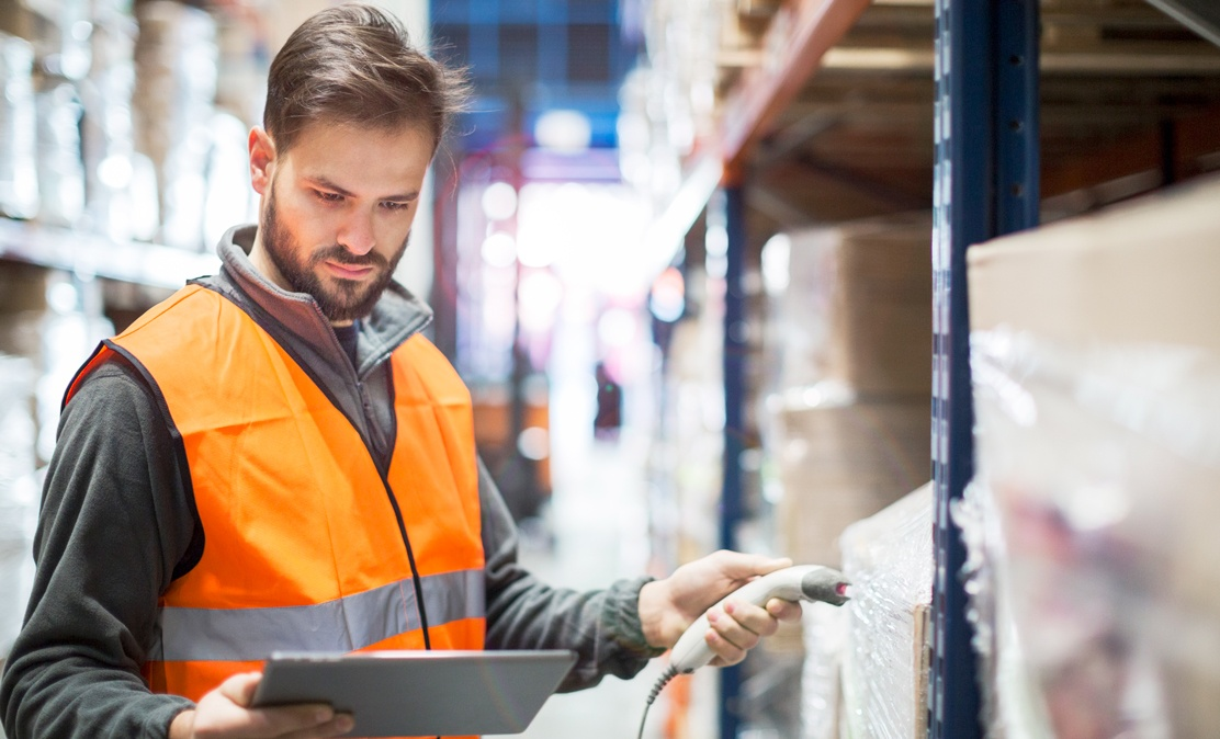 man in orange safety vest scan boxes in warehouse to monitor via iot location tracking